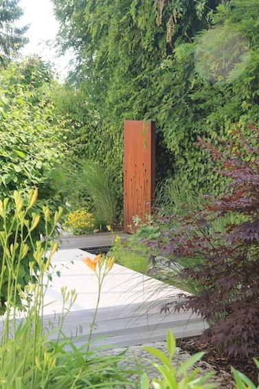 Die Bepflanzung besteht aus Fächerahorn, Taglilien, Gräsern, Hosta und verschiedenen Wasserpflanzen im Bachlauf (Zolling bei Freising)