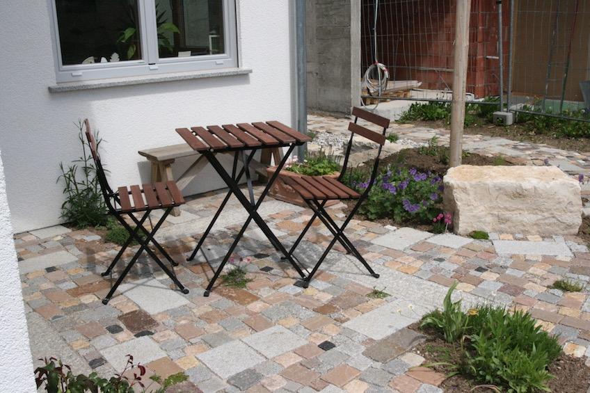 Kleiner Sitzplatz mit gemischtem Pflaster, dass für kleine betretbare Polsterstauden wie  Thymian, Sternmoos oder römische Kamille unterbrochen wurde. (München)