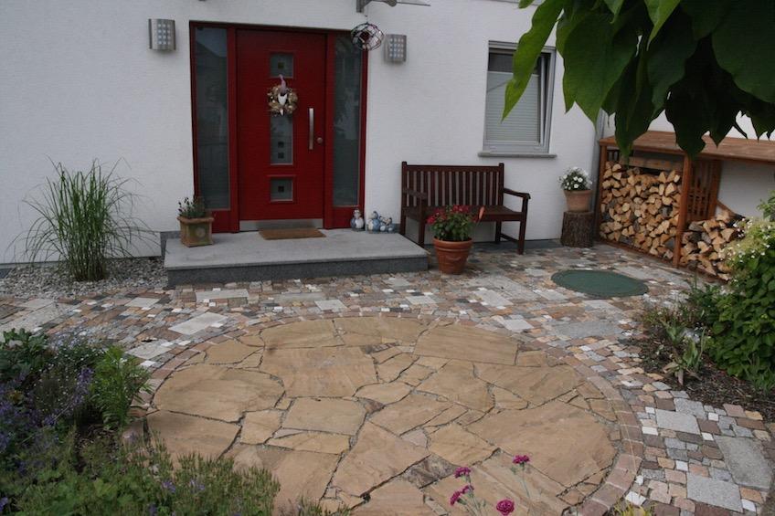 Eingangsbereich mit einem Kreis aus Sandstein und buntem gemischten Pflaster.  (München)