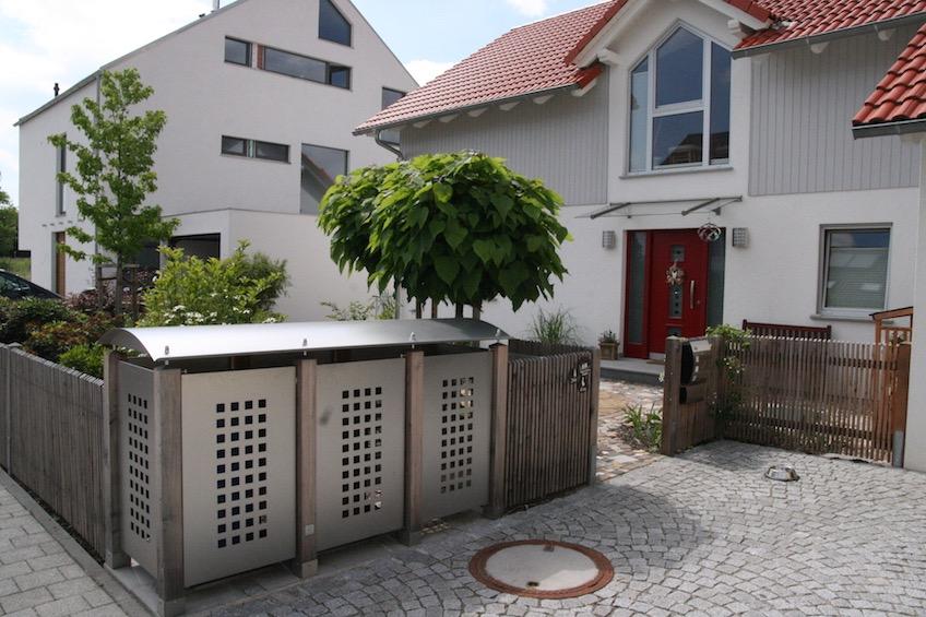 Mülltonnenhäuschen aus Edelstahl, Trompetenbaumkugeln im Hintergrund.  (München)