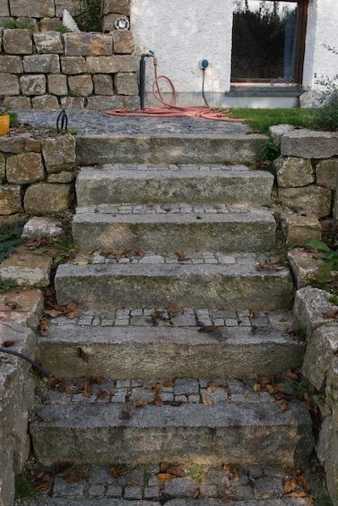 Treppe mit gebrauchten Granit Randsteinen. Auftritte ausgepflastert mit gebrauchtem Granit Kleinstein und Mosaik. Mauereinfassung aus Muschelkalk.  (Attenkirchen bei Freising)