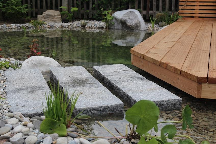 Flach gelegte Granit Randsteine dienen als Weg übers Wasser auf das Holzdeck. (München)