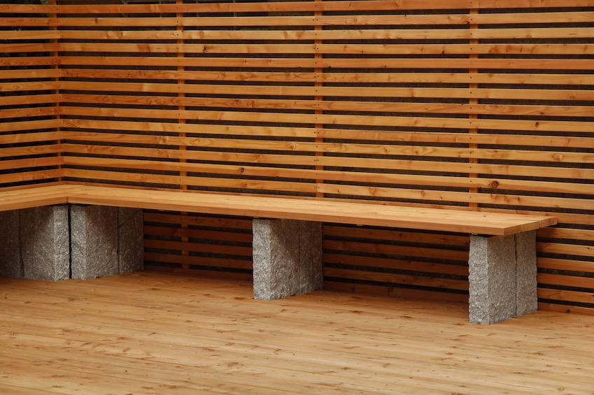 Mit dem Sichtschutz aus Lärche wurde eine Garagenwand verkleidet. Davor wurde eine Holzterrasse gelegt, die über eine Teichfläche ragt. Eine Sitzbank mit Holzauflage lädt zum Verweilen ein. (München)