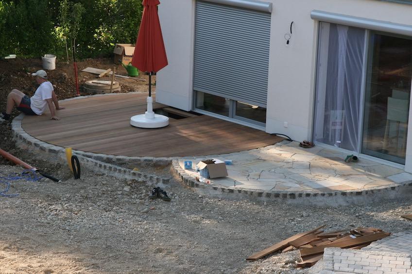 Runde Holzterrasse mit Einfassung aus Granit Großstein, die von einer Steinterrasse mit Belag aus Quarzit angeschnitten wird. (Deisenhofen - Oberhaching)