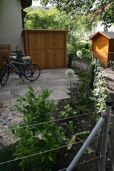 Fahrradstellplatz mit den alten Terrassenplatten aus Waschbeton und einzelnen Streifen mit Granit Kleinstein. Gartenschrank nach Maß der Firma Scholbeck. (Garching bei München)