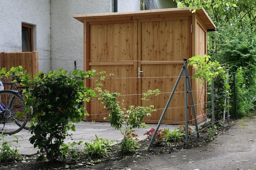 Gartenschrank der Firma Scholbeck. Zaun aus Edelstahlseilen mit Berankung von Kletterpflanzen. (Garching bei München)