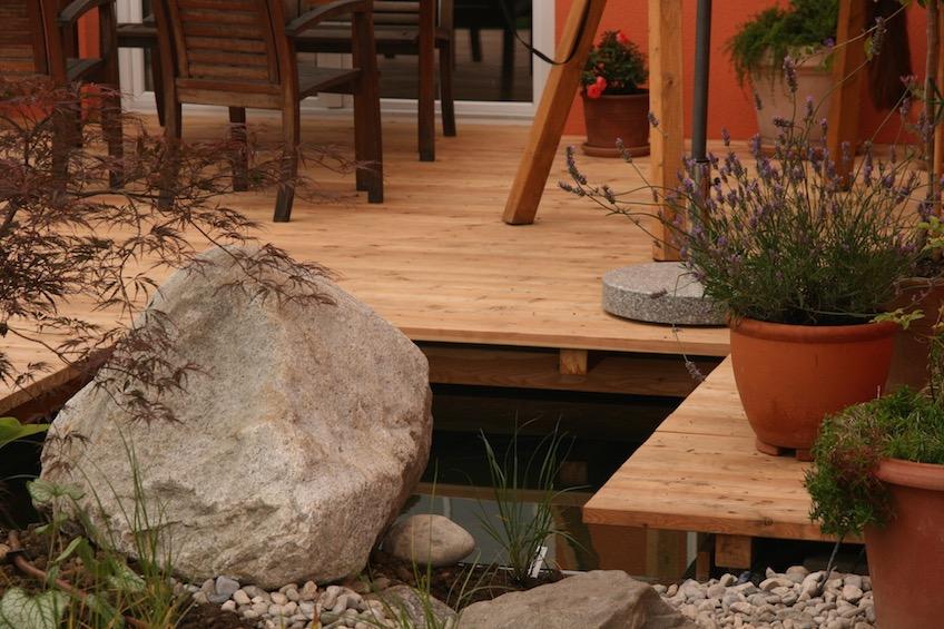 Holzdeck mit angrenzender Wasserfläche und Findling. (Poing bei München)