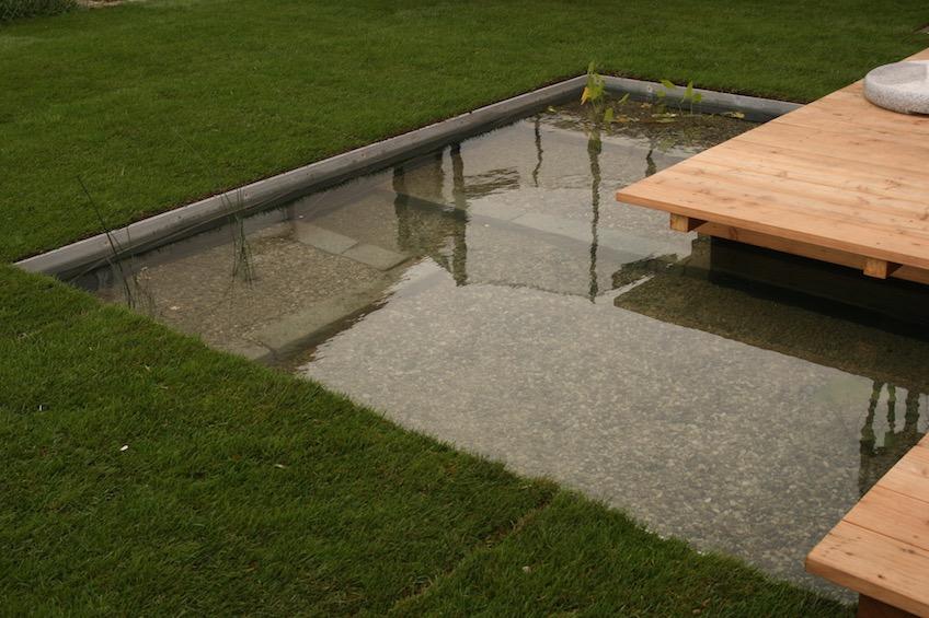 Mit Stahlkanten gefasste formale Wasserfläche und über das Wasser ragendes Holzdeck. (Poing bei München)