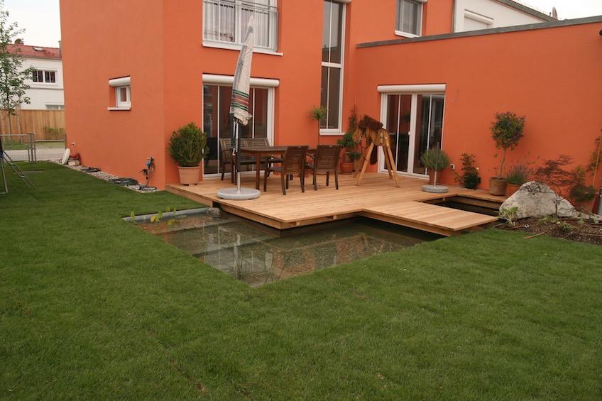 Holzdeck, Wasser und Steg übers Wasser auf den Rasen (Poing bei München)