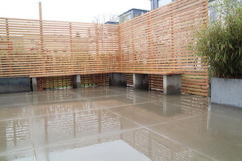 Terrasse mit großformatigen Betonplatten, Sichtschutz aus Holz und Bank mit Sitzauflage aus Holz. (Freising)