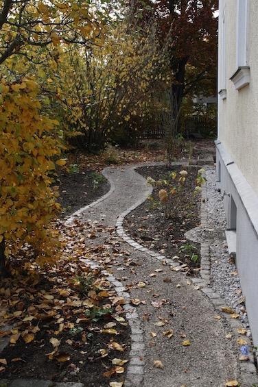 Geschwungener Weg mit Einfassung aus gebrauchtem Granit, befestigt mit wassergebundener Decke. (München)