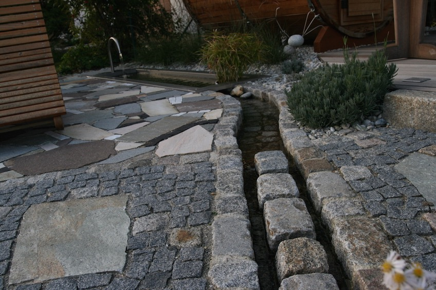 An der Stelle wo der Bachlauf den Gartenweg kreuzt, fliesst er zwischen einer Reihe Granit Großstein hindurch, um das Laufen zu erleichtern. (Mauern bei Moosburg)