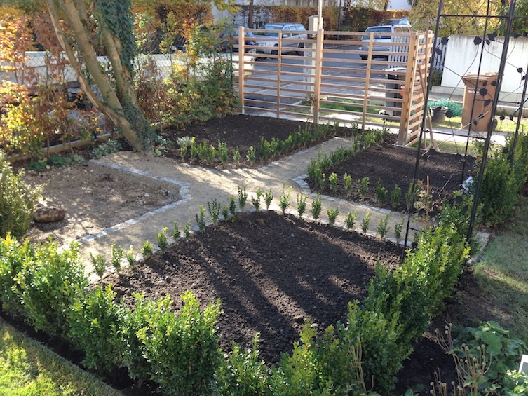 Klassischer Bauerngarten mit Wegekreuz und Einfassung aus Buchs. Ein Viertel der Pflanzliche wird befestigt als kleiner Sitzplatz zum Verweilen. (München)