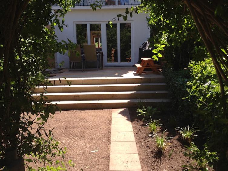 Garten, der mit einer Treppe aus Blockstufen über die ganze Breite großzügiger wirkt. (München)