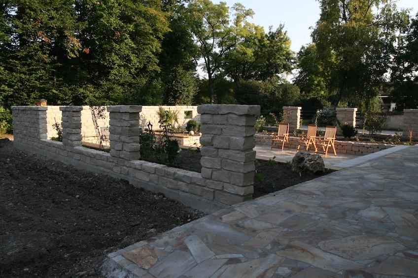 Gartenraum mit Terrassenfläche, Staudenbeeten, Wasserbecken und Sichtschutz aus Stein. (Freising)